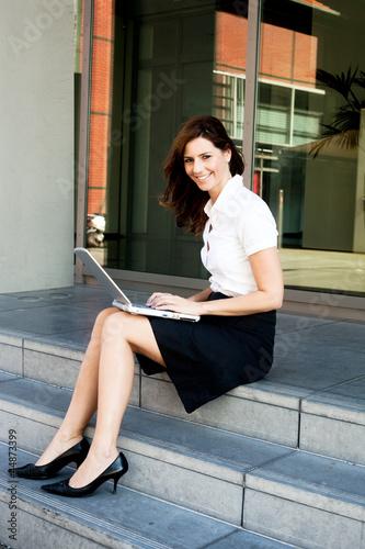 Frau mit Laptop sitzt auf  Treppe