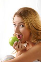 Portrait of pretty girl eating green apple