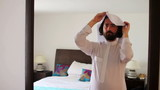 Saudi arabian man dressing at home