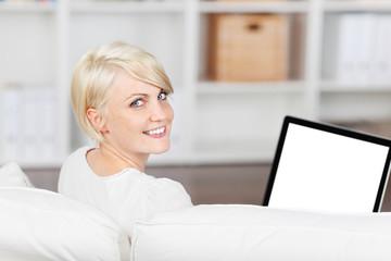 lächelnde frau sitzt auf dem sofa mit ihrem laptop