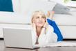 frau mit laptop liegt entspannt auf dem fußboden