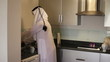 Saudi Arabian man washing dishes at home
