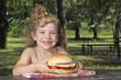 little girl with big sandwich sitting in park