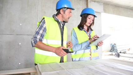Workteam checking blueprint inside house under construction