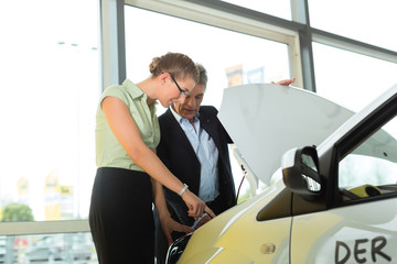 man and woman in car dealership looking under  a hood