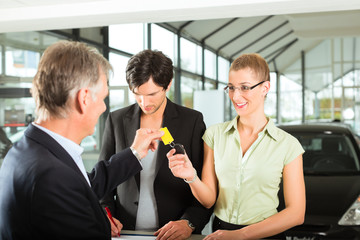 Car sales - dealer handing woman auto key