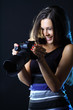 Woman with camera on a dark background looking at her great shot