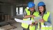 Workteam checking blueprint inside house under construction
