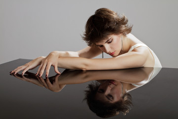 Glamorous young woman rests bare crossed arms on mirrored surfac