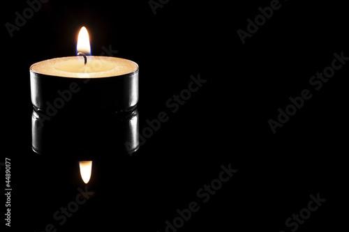 ein teelicht auf schwarzer spiegelnder oberfläche