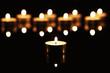ein teelicht vor vielen teelichtern auf schwarzem spiegel