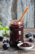 Homemade plum jam on wooden table