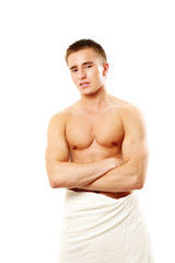 A nude young man covering himself with a towel