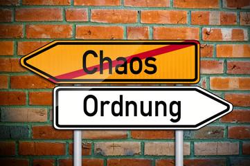 Wegweiser auf Ziegelsteinwand mit Chaos und Ordnung