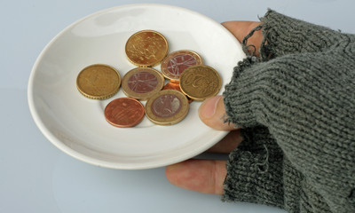 saucer with coins inside held by a poor man