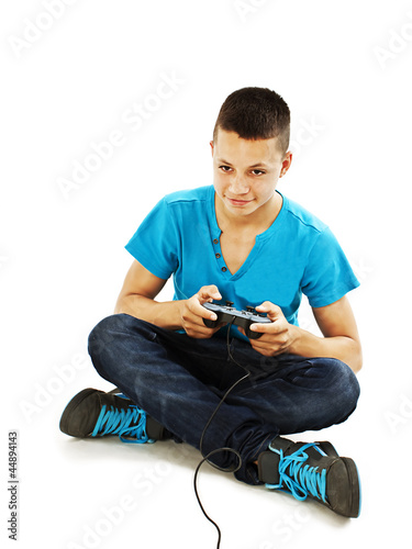 Teen plays on the joysticks sitting on the floor