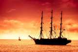 Tall ship sailing in red sunset