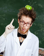 Mad professor with a green apple on his head shows forefinger