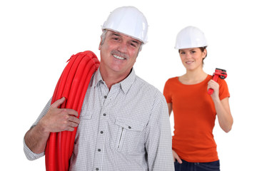 Experienced tradesman with his assistant in the background