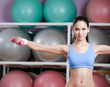 Physically strong woman training with dumbbells in gym