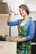 Attractive woman in striped apron cooks vegetables