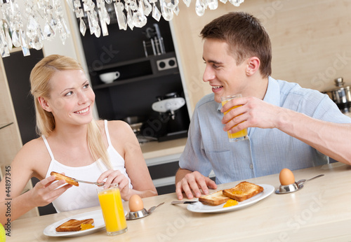 Husband and wife have a snack in the modern comfortable kitchen
