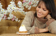 Happy Caucasian woman sitting at a table with a cake