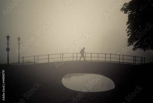 Lonely walker in a misty morning