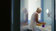 Active retired woman doing chores and cleaning bathroom at home