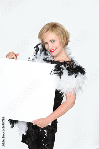 Woman in a vintage dress holding an empty publicity poster