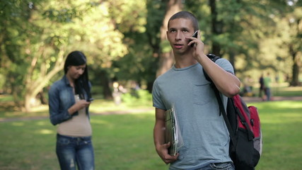 Young student talking on cellphone in the park, steadicam shot