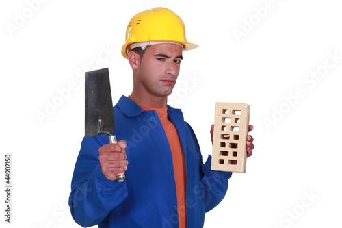 Mason holding brick and trowel