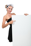 Woman in a French maid's outfit pointing at board
