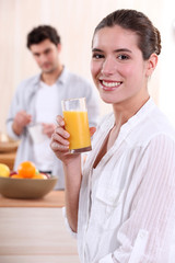 Woman drinking a glass of orange juice for breakfast