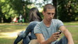 Young man with smartphone in the park, steadicam shot
