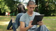 Young happy student with tablet computer in the park