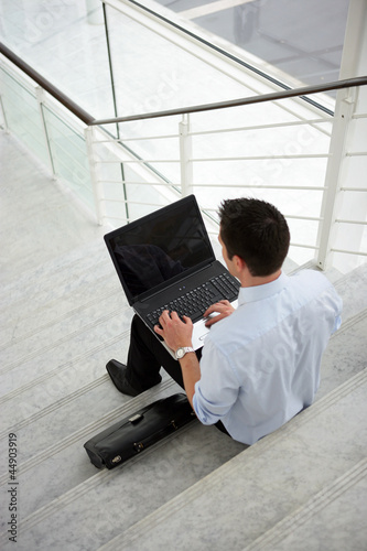 Businessman sitting on some steps with a laptop