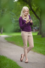 Woman Using Smart Phone In Park