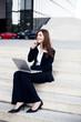Telefonierende Geschäftsfrau mit Laptop sitzt auf einer Treppe