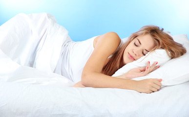 young beautiful woman sleeping on bed on blue background