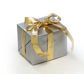 Geschenk mit Goldband auf weißem Hintergrund