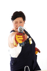 Playful woman taking aim with power drill