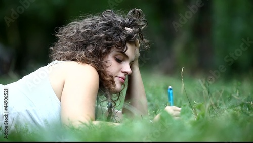 Young woman writing in park