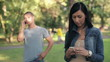Young couple with cellphone and smartphone in the park