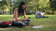 Young teenage student with smartphone in the park