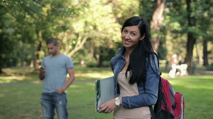 Portrait of young happy female student in the park