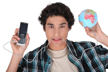 Young man with his cellphone plugged into the world