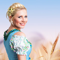 junge blonde Frau in Trachtenmode vor Weizenfeld-Hintergrund