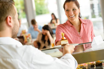 Waiter giving woman cake plate at cafe