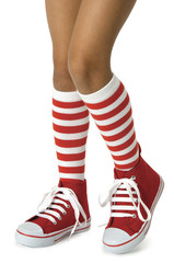 Girl with striped socks and red shoes. Clipping path included.